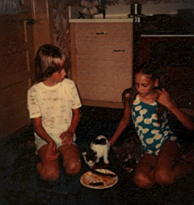 my step-sister and I feed ribs to the cats--1977
